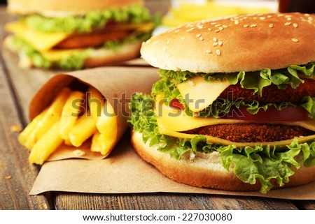 Big burger on brown wooden background - stock photo
