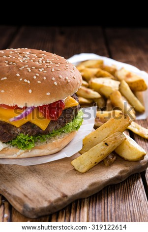 Big Burger with homemade French Fries on rustic wooden background