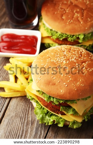 Big burgers on brown wooden background - stock photo