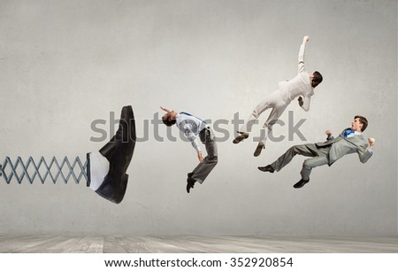 Big businessman foot on spring kicking business people  - stock photo