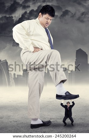 Big businessman try to trample his little employee, symbolizing bossy businessman - stock photo