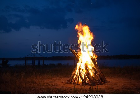 Big campfire at the river after sunset  - stock photo