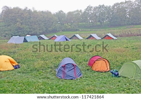 big campsite with tents of boy scouts on a cold winter day - stock photo