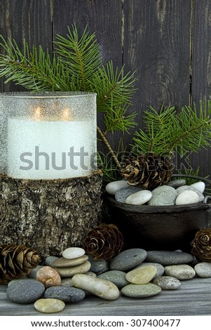 Big candle in glass holder wrapped in bark with a collection of stones and some pinecones and pine branch.