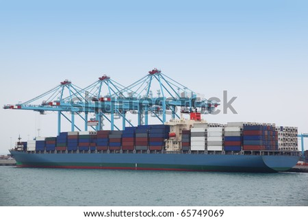 Big cargo boat docked to industrial port with several blue cranes - stock photo