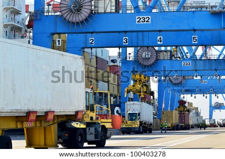 Big cargo container ship freighter vessel in a container seaport during transportation of cargo in containers by cranes and lorry truck. - stock photo