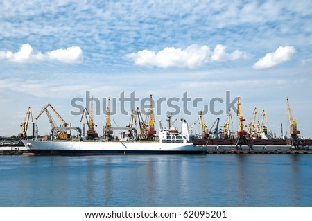 big cargo ship at big sea port with lots of cranes, blue cloudy sky in background