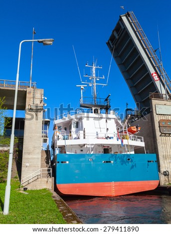 Big cargo ship comes to the narrow gateway of Tsvetochnoye lock on the Saimaa Canal, a transportation canal that connects lake Saimaa with the Gulf of Finland near Vyborg, Russia. Back view