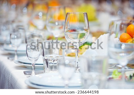 Big celebratory served table with glasses and plates - stock photo