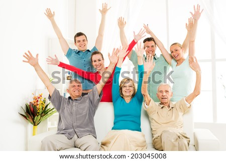 Big cheerful family enjoying at home and rejoices with open arms  - stock photo