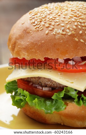 Big cheeseburger with lettuce and tomato on a plate