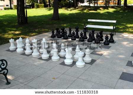 big chess set in the park with benches