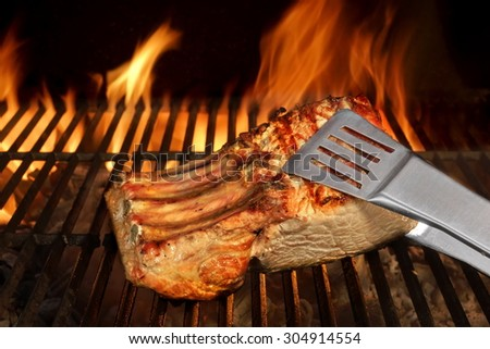 Big Chop Of Pork Ribs On The Hot BBQ Grill With Flames On The Black Background. Cookout Scene - stock photo