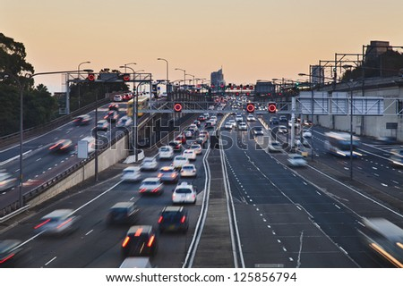 big city highway motor road with heavy traffic of cars and vehicles at sunset blurred lights - stock photo