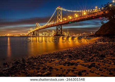Big City lights on a brightly lit Bay Bridge in San Francisco - stock photo