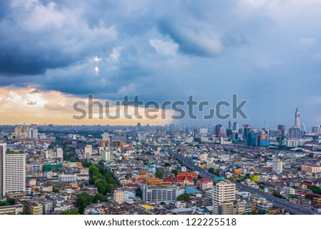 big city with rain cloud falling in background - stock photo