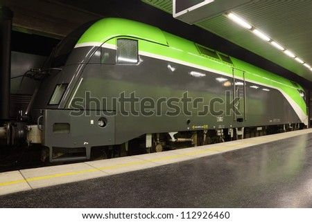 Big clean green passenger commuter train on rails in subway.