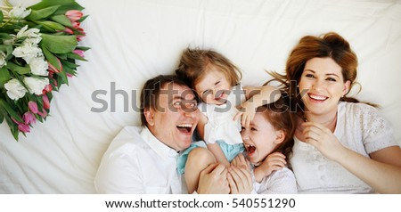 Big close-knit family from four people cheerfully spends time for beds. Two little girls lie between parents. They are naughty and laugh. Good mood of children gives pleasure to parents.