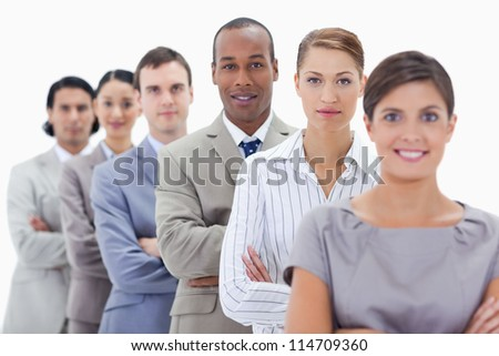Big close-up of a business team in a single line crossing their arms with focus on the first man - stock photo