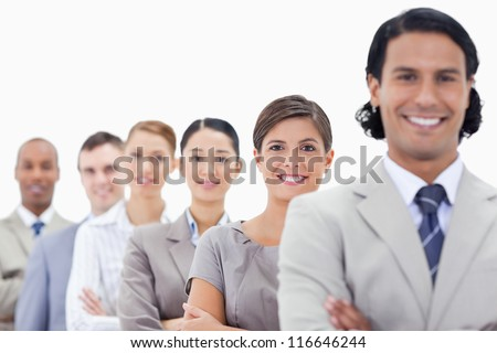 Big close-up of happy colleagues crossing their arms in a single line looking straight with focus on the first woman - stock photo