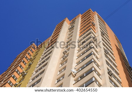 Big colorful apartment building with conditioners against blue sky in residential settlement