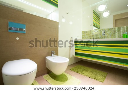 Big colorful bathroom with green units and marble floor - stock photo