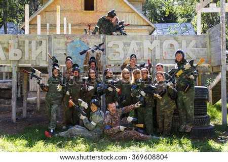 Big company of paintball players and kissing couple on background and sign White Castle - stock photo