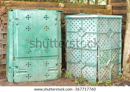 Big compost plastic boxes in green full of biodegradable organic and food scraps in the backyard for making nutrient-rich soil - stock photo