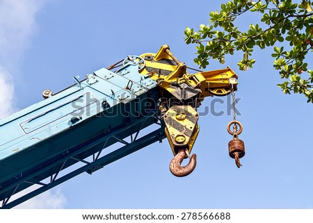 Big  construction crane with hook for heavy lifting high up to the tree - stock photo