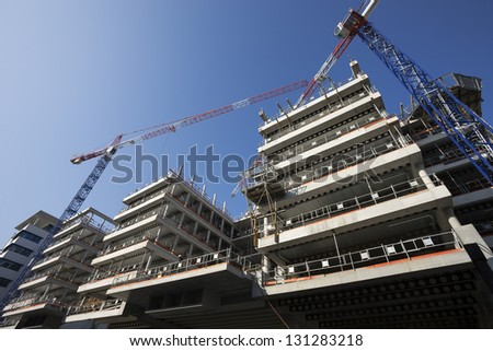 big construction site with cranes and blue sky - stock photo