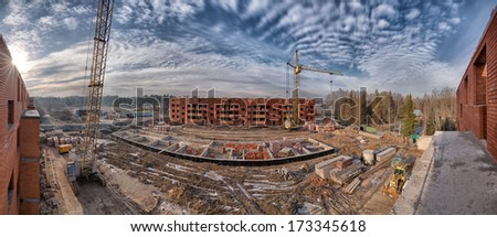 Big construction site with cranes in winter panorama - stock photo