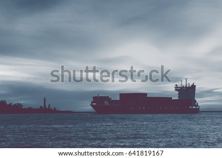 Big container ship arriving from Baltic sea at red sunset sky