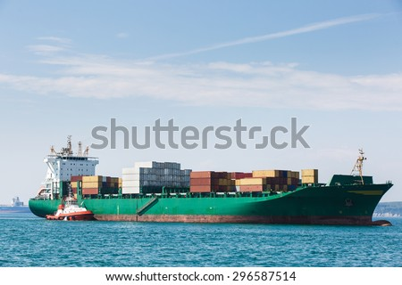 Big container ship, loaded with various colorful containers, waiting to be assisted and escorted to the port by a towboat. Global transportation, global business, consumerism concept and background.