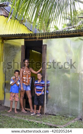 BIG CORN ISLAND, NICARAGUA-NOV. 16: A proud young mother and two boys are seen by new zinc sheet metal house in jungle in Big Corn Island, Nicaragua, Central America on November 16, 2015. - stock photo