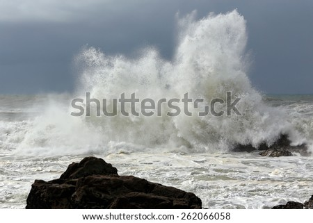 Big crashing wave against a rocky beach