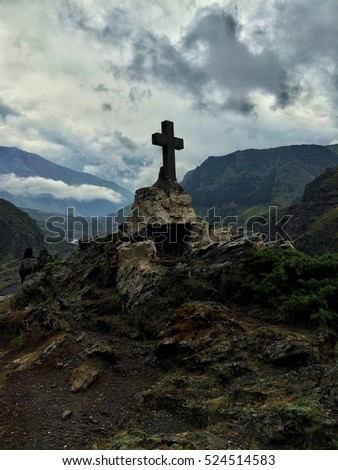 Big cross monument in mountain with beautiful cloudy sky and green grass