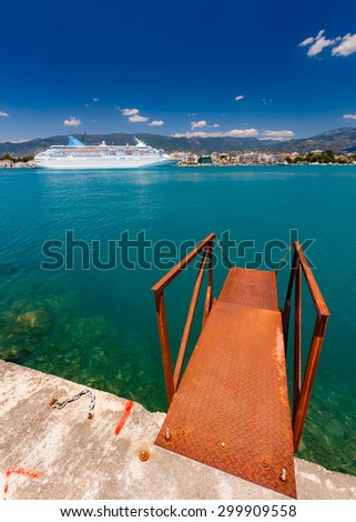 Big cruise ship anchored in port against a blue sky and clouds with rusty embarking platform in the foreground in Greece - stock photo