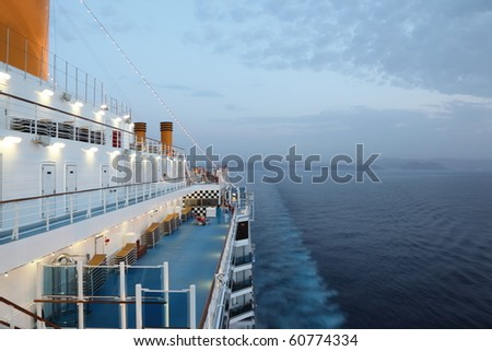 big cruise ship riding in evening. light on. few of people on deck. - stock photo