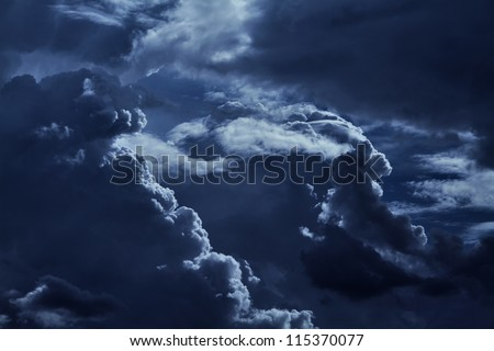 Big cumulus clouds in the night sky.