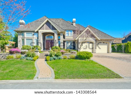 Big custom made luxury double garage doors house with long driveway and nicely paved curved doorway in the suburbs of Vancouver, Canada. - stock photo