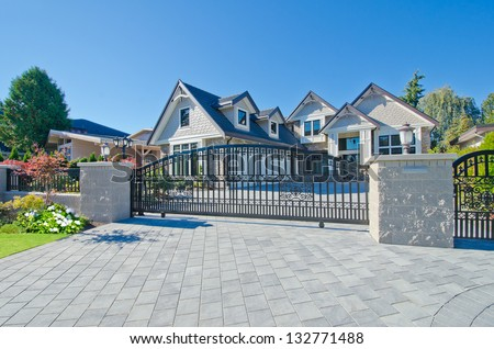 Big custom made luxury house behind the gates and nicely paved driveway in the suburbs of Vancouver, Canada. - stock photo