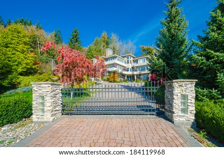 Big custom made luxury house behind the gates with nicely paved driveway gin the suburbs of Vancouver, Canada. - stock photo