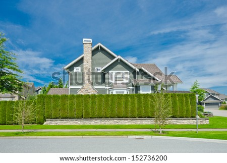 Big custom made luxury house behind the green nicely trimmed fence in the suburbs of Vancouver, Canada. Keeps privacy and security. Landscape trimming design. - stock photo