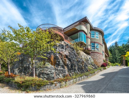 Big custom made luxury house on the rocks with nicely landscaped and trimmed front yard in the suburbs of Vancouver, Canada. - stock photo