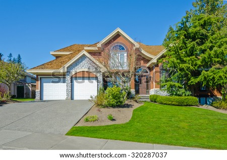 Big custom made luxury house with double doors garage and nicely trimmed and landscaped front yard and paved driveway in the suburbs of Vancouver, Canada.