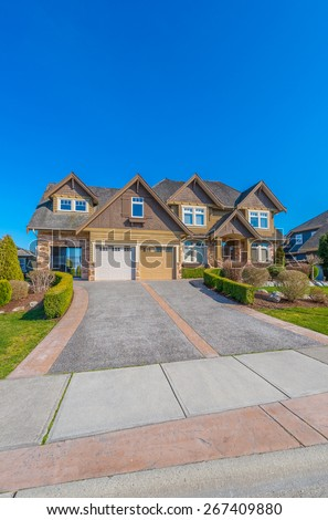 Big custom made luxury house with landscaped front yard and nicely paved driveway to garage in the suburb of Vancouver, Canada. Vertical. - stock photo