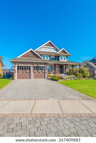 Big custom made luxury house with landscaped front yard and nicely paved driveway to garage in the suburb of Vancouver, Canada. Vertical.