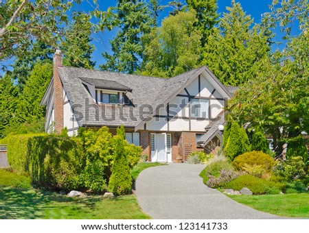 Big custom made luxury house with long curved driveway and nicely landscaped front yard in the suburbs of Vancouver, Canada.