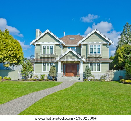 Big custom made luxury house with long doorway and nicely decorated and trimmed front yard in the suburbs of Vancouver, Canada. - stock photo