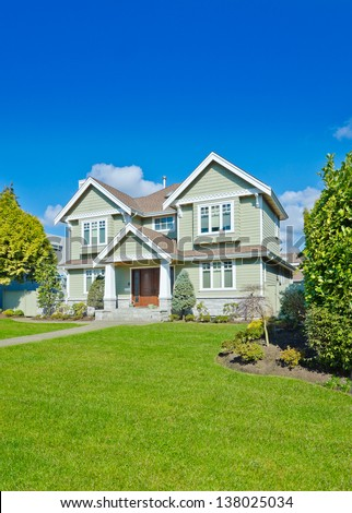 Big custom made luxury house with long doorway and nicely decorated and trimmed front yard in the suburbs of Vancouver, Canada. Vertical. - stock photo